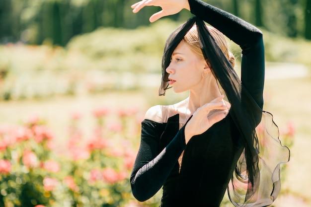 Dramático retrato de jovem de vestido preto com véu na manga dela posando no parque de verão