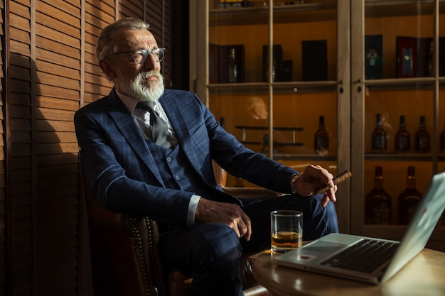 Dramaturgo sênior que olha o portátil, criando a novela ao sentar-se no bar.