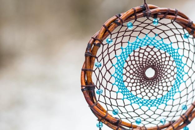 Dreamcatcher azul e marrom feito de contas de couro de penas e cordas, penduradas