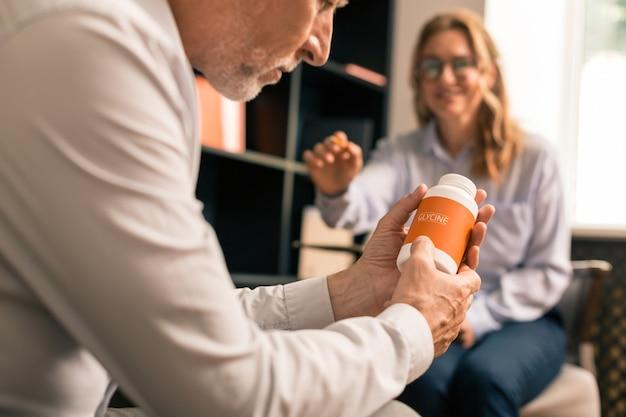 Droga hipnótica. vista lateral de um homem sério segurando medicamentos soporíferos nas mãos enquanto está sentado ao lado de uma mulher loira feliz