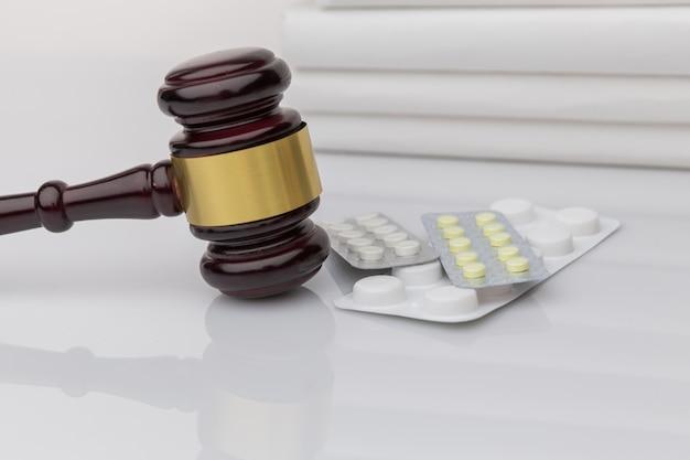 Drogas e lei. martelo de juiz e pílulas coloridas em uma mesa de madeira