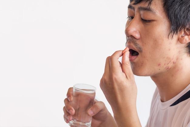 Drogas na mão paciente, colorido de comer medicamentos no fundo branco