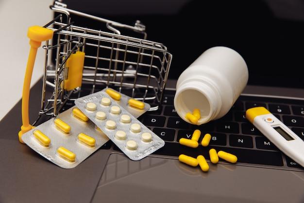 Drogas no carrinho e ferramentas médicas no laptop, conceito de compras online.