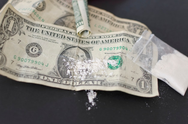Drogas viciantes em dinheiro e cocaína usam pó branco como a cocaína