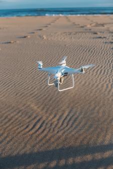 Drone aéreo privado pousa na areia da praia