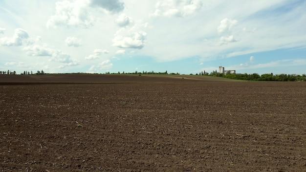 Drone aéreo vista voo sobre enorme campo arado e céu azul. linha do horizonte, horizonte. terra negra. agricultura, atividades agrícolas. paisagem rural do país. desenterrando a terra. agronomia, farmin