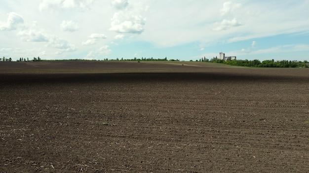 Drone aéreo vista voo sobre enorme campo arado e céu azul.