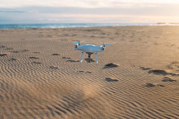 Drone aéreo voando baixo para o solo na praia