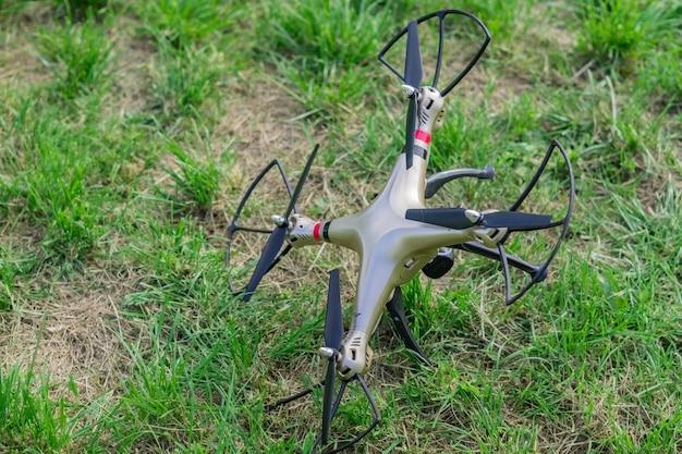 Drone caído na grama verde após a desconexão do controle remoto