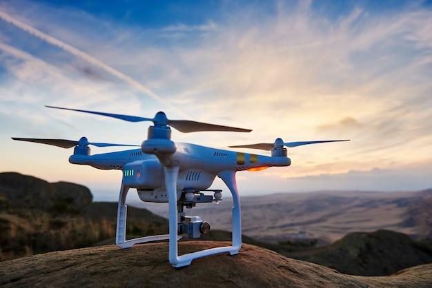 Drone com câmera digital de alta resolução pronto para voar ao pôr do sol em
