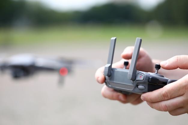 Drone de gravação de vídeo moderno controlado com mãos masculinas segurando o controle remoto