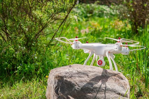 Drone de pé sobre uma pedra grande e preparado para decolar.