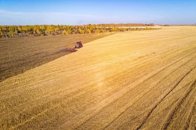 Drone de vista aérea do campo de colheita com trator corta a grama seca. campo de outono amarelo com um palheiro após a vista superior da colheita. colheita nos campos. estocar feno para o inverno. vista do topo.