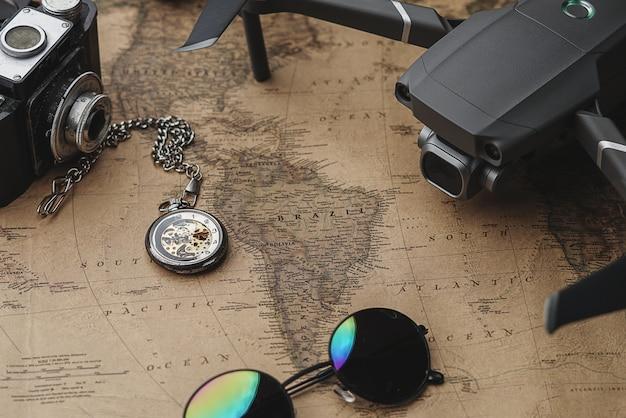 Drone entre acessórios do viajante no mapa antigo vintage
