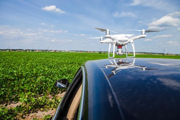 Drone no teto do carro em um fundo do campo verde