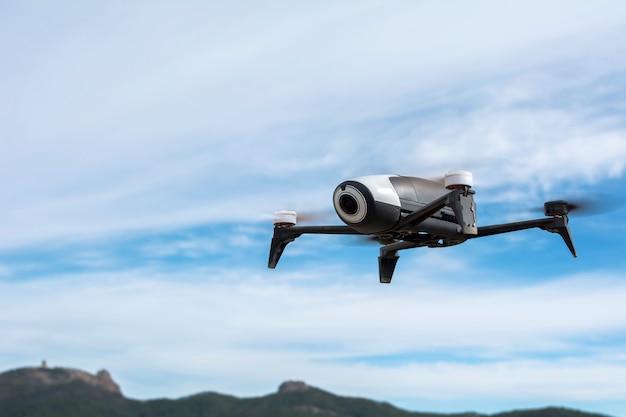 Drone preto e branco, com câmera de vídeo, pendurado no ar