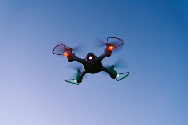 Drone quad helicóptero contra o pôr do sol