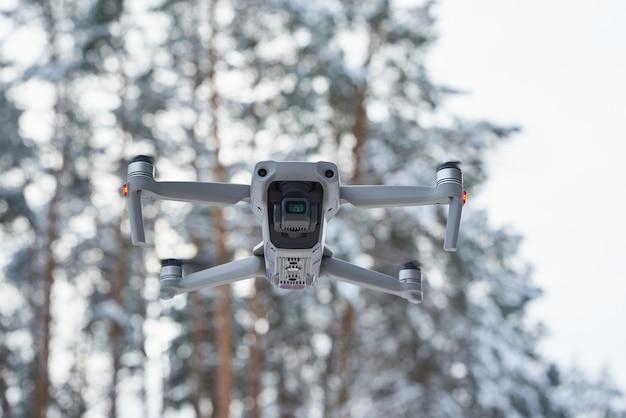 Drone quadcopter com câmera voando na floresta de inverno