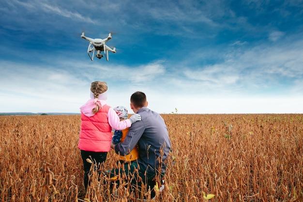 Drone sendo operado por pai e filho no campo
