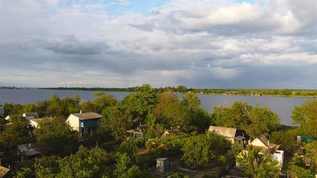 Drone sobrevoa um rio ondulante de cor azul cercado por uma vila local com vários edifícios