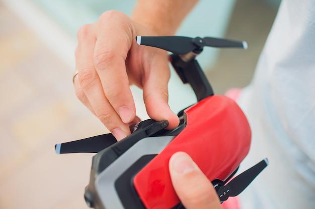 Drone vermelho pegando o controle pelas mãos do homem. estabelece hélices