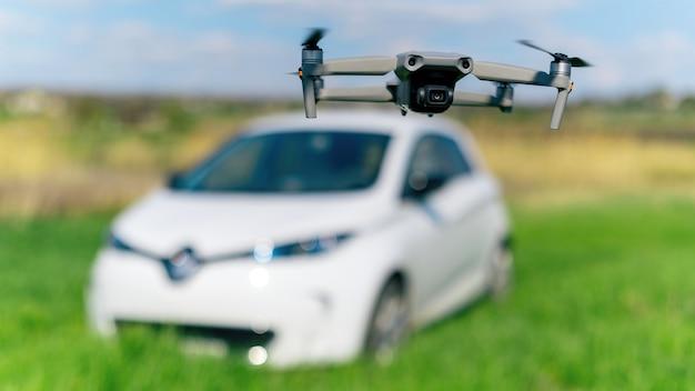 Drone voador atirando em um carro elétrico estacionado na natureza