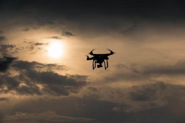 Drone voador com câmera no céu ao pôr do sol