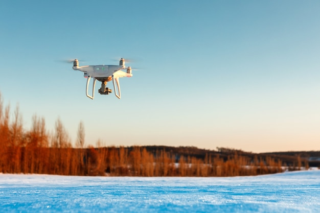Drone voando acima do campo coberto de neve em um dia ensolarado de inverno