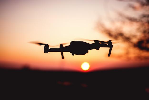 Drone voando ao pôr do sol. silhueta de drone contra céu colorido.