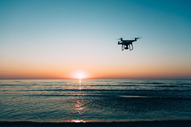Drone voando em um fundo por do sol do mar