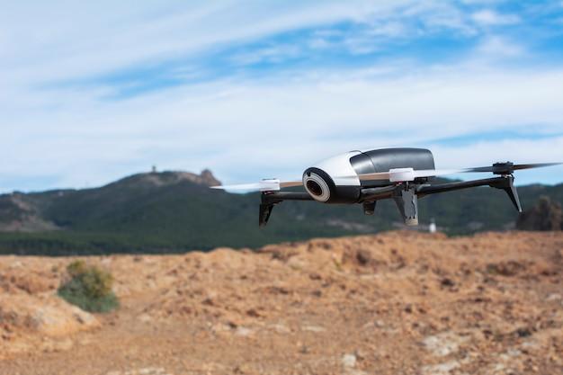 Drone voando sobre o campo, com terra, montanhas e céu azul ao redor.