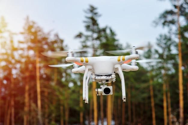 Drone voando sobre um fundo de árvores da floresta