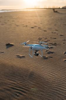 Drone werial voando baixo para o solo na praia