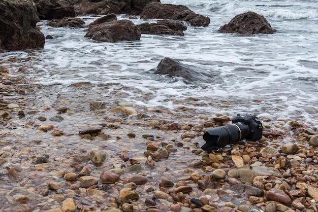 Dslr câmera na praia de pedra molhada da onda do mar de água