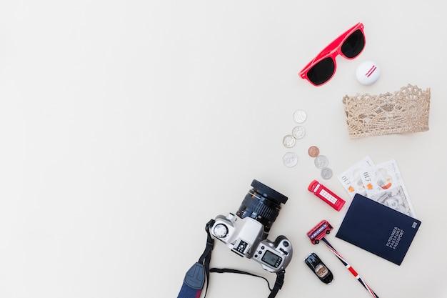 Dslr câmera, passaporte, moedas, óculos escuros e brinquedos em pano de fundo brilhante