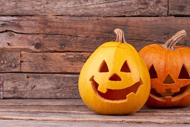 Duas abóboras de halloween engraçadas em placas de madeira.