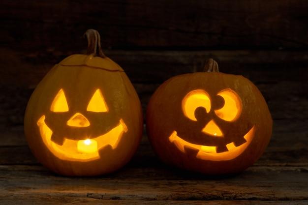 Duas abóboras engraçadas com velas brilhantes halloween abóbora jackolantern com cara feliz em backg escuro ...