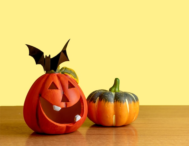Duas abóboras laranja ficam em uma mesa sobre um fundo amarelo. um morcego preto senta-se em uma abóbora.