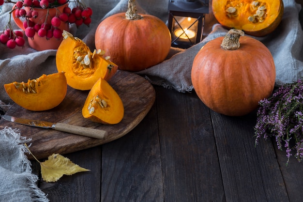 Duas abóboras, uma abóbora em uma seção, um castiçal em forma de lanterna, urze e folhas de outono
