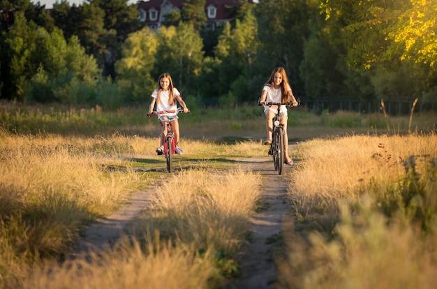 Duas adolescentes andando de bicicleta em um prado ao pôr do sol