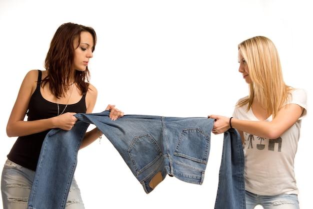 Duas adolescentes atraentes em pé brigando por causa de jeans, cada uma puxando um retrato de meio corpo em branco de uma perna