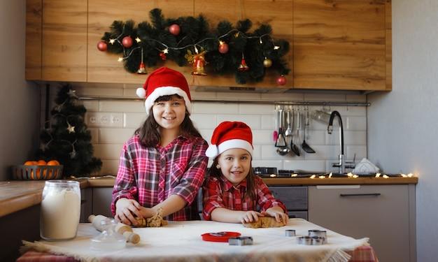 Duas adolescentes com camisas xadrez vermelhas e chapéus de natal estão fazendo biscoitos de gengibre com massa e rindo alegremente.