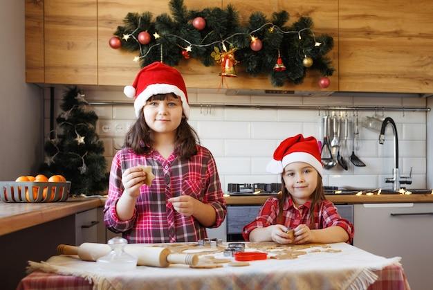 Duas adolescentes com camisas xadrez vermelhas e chapéus de natal estão fazendo biscoitos de gengibre com massa.