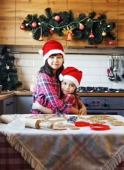 Duas adolescentes com chapéus de natal e camisas xadrez vermelhas se abraçam na cozinha antes do natal.
