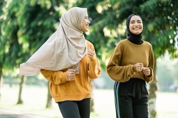 Duas adolescentes com véu praticam esportes ao ar livre enquanto correm juntas no parque