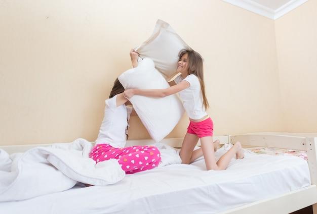 Duas adolescentes de pijama brigando com travesseiros