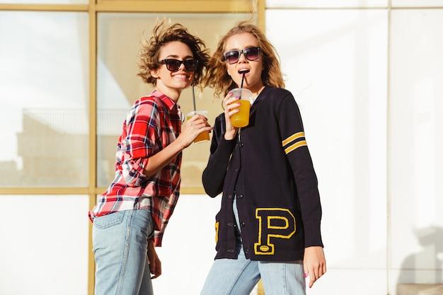 Duas adolescentes felizes em óculos de sol, bebendo suco de laranja