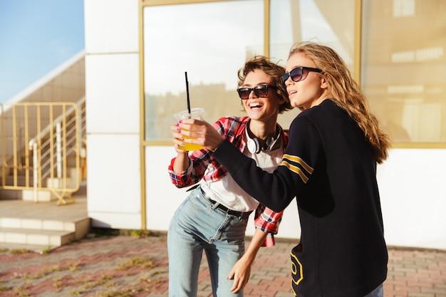 Duas adolescentes felizes em óculos de sol brindando