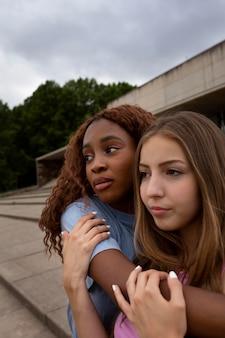 Duas adolescentes posando juntas enquanto passam o tempo ao ar livre