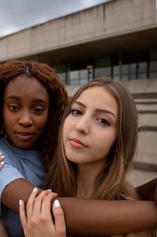Duas adolescentes posando juntas para uma selfie ao ar livre